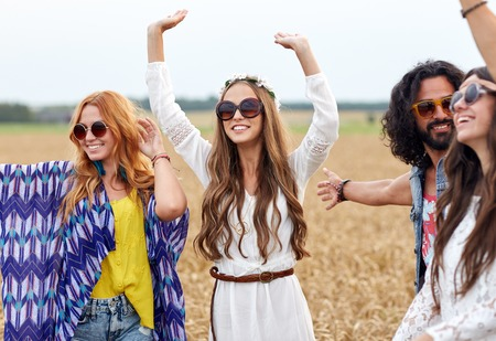 holiday music: nature, summer, youth culture and people concept - happy young hippie friends dancing on cereal field