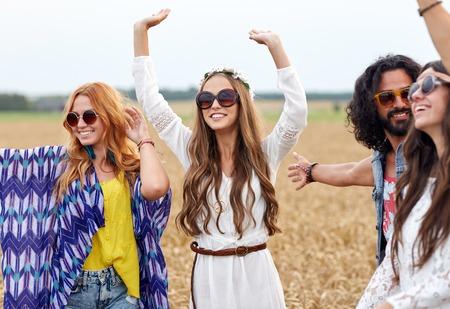 natuur, de zomer, jeugdcultuur en mensen concept - happy hippie vrienden dansen op graangewassengebied Stockfoto
