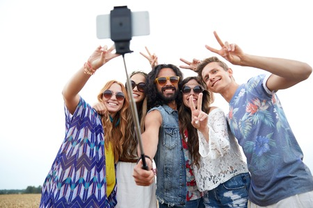 hippy: nature, summer, youth culture, technology and people concept - smiling young hippie friends in sunglasses taking picture by smartphone on selfie stick and showing peace gesture on cereal field Stock Photo