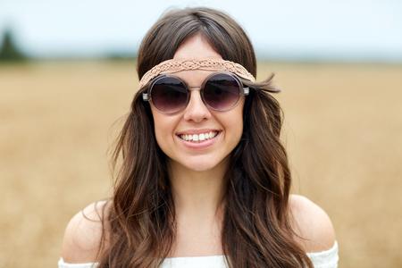 自然、夏、若者の文化と人々 のコンセプト - サングラス アウトドアで若いヒッピー女性を笑顔