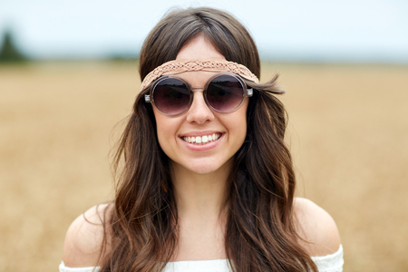 mujer hippie: naturaleza, verano, la cultura juvenil y la gente concepto - sonriente joven hippie mujer en gafas de sol al aire libre