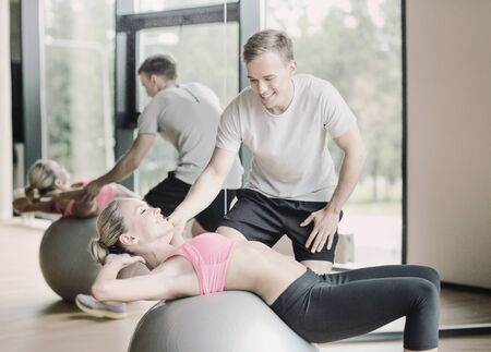 trainers: fitness, sport, exercising and diet concept - smiling young woman and personal trainer in gym Stock Photo