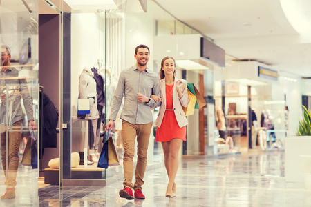 Verkoop, consumentisme en mensen concept - gelukkig jong koppel met boodschappentassen lopen in winkelcentrum Stockfoto