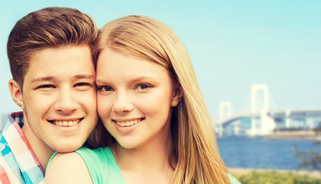 travel japan: travel, tourism, vacation, people and love concept - smiling couple hugging over rainbow bridge in tokyo and river background Stock Photo