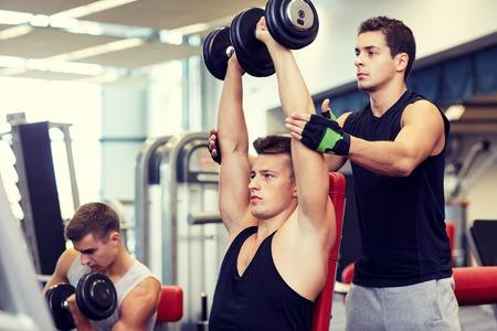 fitness men: deporte, fitness, estilo de vida, levantamiento de pesas y el concepto de personas - grupo de hombres con pesas y los m�sculos entrenador personal en el gimnasio que dobla Foto de archivo