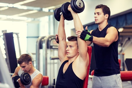 sport, fitness, lifestyle, powerlifting and people concept - group of men with dumbbells and personal trainer flexing muscles in gym Stock Photo