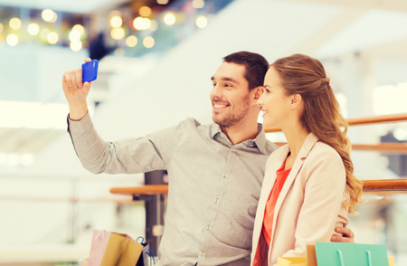 family portrait: sale, consumerism, technology and people concept - happy young couple with shopping bags and smartphone taking selfie in mall