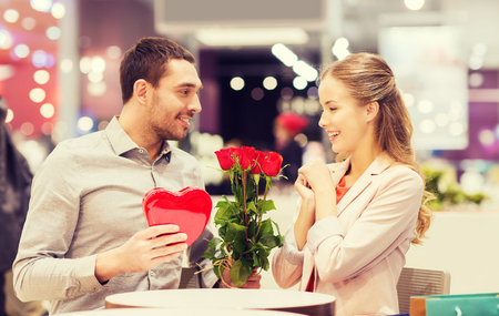 flower boxes: love, romance, valentines day, couple and people concept - happy young man with red flowers giving present to smiling woman at cafe in mall