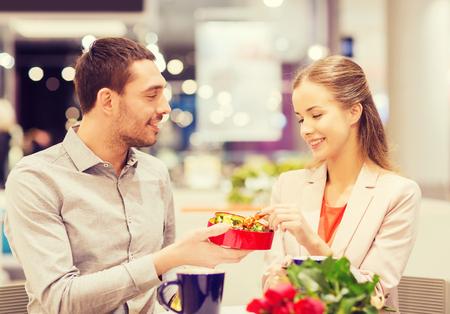 mujer alegre: Amor, romance, día de San Valentín, pareja y concepto de la gente - feliz pareja de jóvenes con flores rojas y abrir la caja de regalo en el centro comercial de café