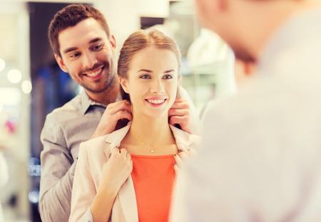 verkoop, consumentisme, cadeautjes, vakanties en mensen concept - gelukkig paar proberen gouden hanger aan bij juwelierszaak in winkelcentrum Stockfoto