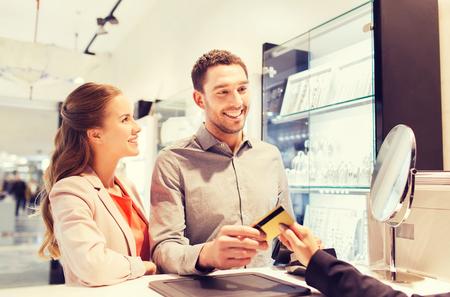 verlobung: Ausverkauf, Konsum, Einkaufs-und Personen-Konzept - glückliches Paar mit Kreditkarte im Juweliergeschäft im Einkaufszentrum Lizenzfreie Bilder