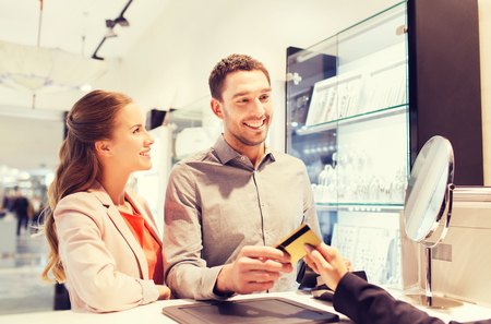 discount card: sale, consumerism, shopping and people concept - happy couple with credit card at jewelry store in mall Stock Photo