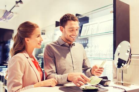 anillo de compromiso: la venta, el consumismo, las compras y la gente concepto - feliz pareja con el dinero para pagar la compra en la tienda de joyas Foto de archivo