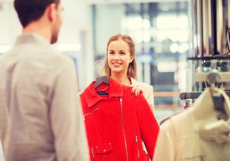 tienda de ropa: venta, compras, consumismo y el concepto de la gente - Feliz pareja de jóvenes que eligen la ropa en una tienda de ropa en el centro comercial