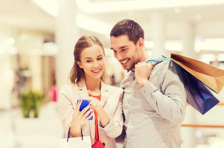 La vente, la consommation, la technologie et les gens notion - heureux jeune couple avec des sacs et Smartphone parler dans centre commercial Banque d'images - 48408862