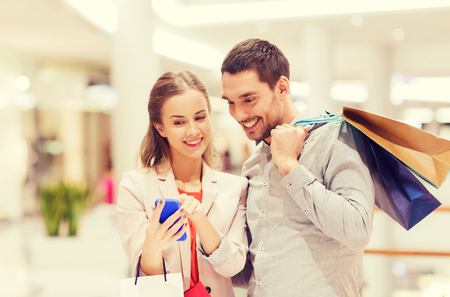 sale, consumerism, technology and people concept - happy young couple with shopping bags and smartphone talking in mall Stock Photo