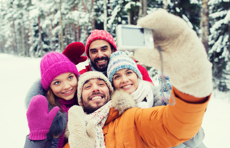 caminar: technology, season, friendship and people concept - group of smiling men and women taking selfie with digital camera in winter forest