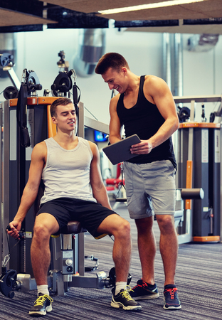 personal training: sport, fitness, equipment, technology and people concept - men with personal trainer and tablet pc computer exercising on gym machine Stock Photo