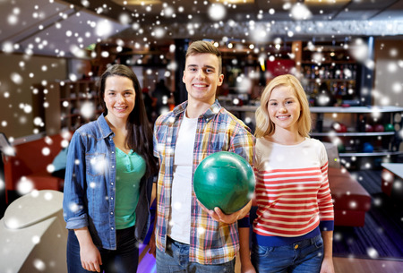 teen couple: people, leisure, sport, friendship and entertainment concept - happy friends in bowling club at winter season