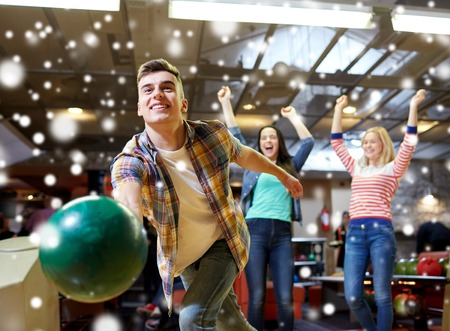 rooting: people, leisure, sport and entertainment concept - happy young man throwing ball in bowling club at winter season