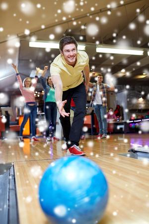 bolos: la gente, el ocio, el deporte y el concepto de entretenimiento - hombre joven feliz que lanza la bola en club de bolos en la temporada de invierno