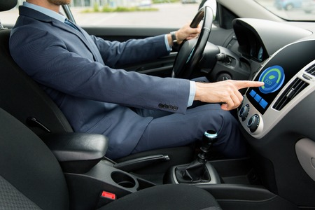 eco car: transport, business trip, technology and people concept - close up of young man in suit driving car and adjusting car eco mode system settings on dashboard computer screen