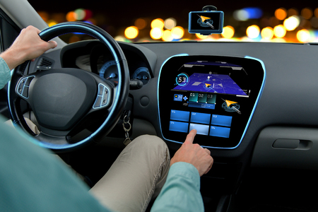 concept car: transport, destination, modern technology and people concept - close up of man driving car with navigation system on board computer