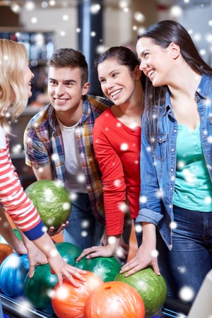 entertainment concept: people, leisure, sport, friendship and entertainment concept - happy friends in bowling club at winter season