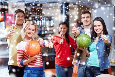bolos: la gente, el ocio, el deporte, la amistad y el concepto de entretenimiento - amigos felices que sostienen bolas y mostrando los pulgares para arriba en club de bolos en la temporada de invierno Foto de archivo