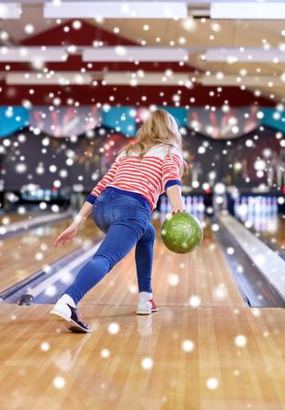 terreno: persone, tempo libero, sport e divertimento concetto - felice giovane donna buttare la palla nel randello di bowling alla stagione invernale Archivio Fotografico