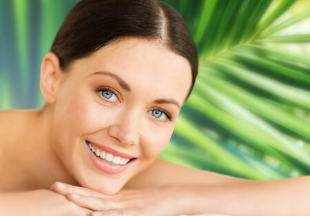 natural face: health and beauty, resort and relaxation concept - woman in spa salon lying on the massage desk Stock Photo