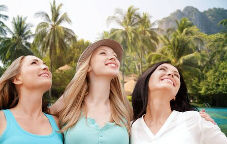 resort beach: summer holidays, people, travel and vacation concept - happy young women looking up over resort beach with palm trees background