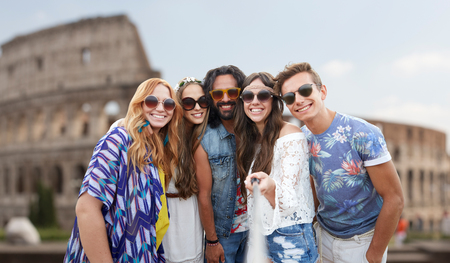 group picture: summer vacation, travel, tourism, technology and people concept - smiling young hippie friends taking picture by smartphone selfie stick over coliseum in rome background Stock Photo
