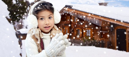 ni�os latinos: winter holidays, season, christmas, people and children concept - happy little girl wearing earmuffs and gloves over wooden country house background and snow Foto de archivo