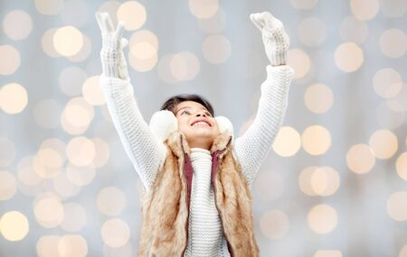 asian style: winter, people, christmas happiness concept - happy little girl wearing earmuffs and gloves over holidays lights background