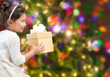 asian preteen: holidays, presents, christmas, childhood and people concept - smiling little girl with gift box over lights background Stock Photo