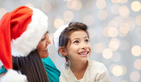 asian preteen: christmas, holidays, family, childhood and people concept - happy mother and little girl in santa hats over lights background