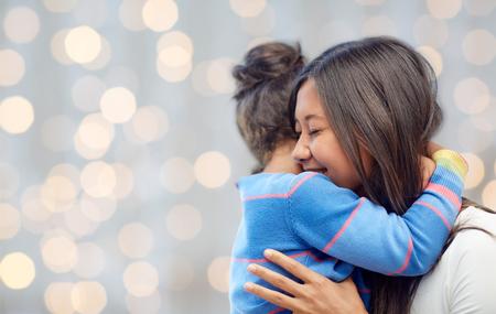 madre soltera: familia, los hijos, el amor y la gente feliz concepto - feliz madre e hija abrazando sobre fondo de las luces