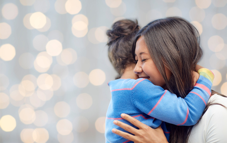 embrace: family, children, love and happy people concept - happy mother and daughter hugging over lights background