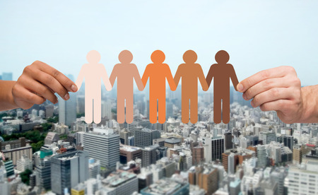 unity: community, unity, population, race and humanity concept - multiracial couple hands holding chain of paper people pictogram over city background