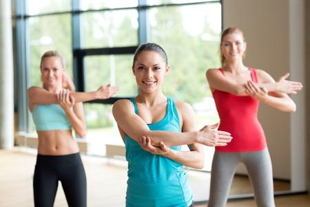 aerobics: fitness, deporte, entrenamiento, gimnasio y estilo de vida concepto - grupo de mujeres que trabajan en el gimnasio