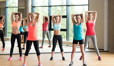 fitness training: fitness, sport, training, gym and lifestyle concept - group of women working out in gym