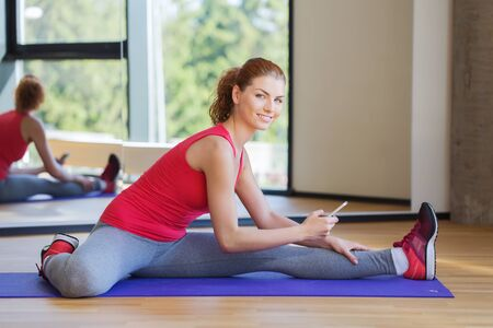 cell phone: fitness, sport, technology and people concept - smiling woman with smartphone stretching leg on mat in gym Stock Photo