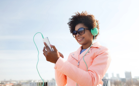 listening: technology, lifestyle and people concept - smiling african american young woman or teenage girl with smartphone and headphones listening to music outdoors