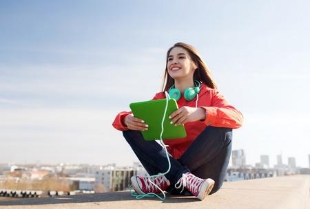 기술, 라이프 스타일, 음악, 사람들 개념 - 야외 태블릿 pc 컴퓨터와 헤드폰 젊은 여자 또는 웃 고 십 대 소녀