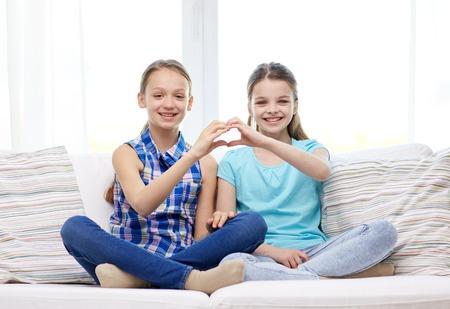 niños sentados: gente, niños, amigos y el concepto de la amistad - niñas felices, sentado en el sofá y mostrando un signo de la mano en forma de corazón en el país
