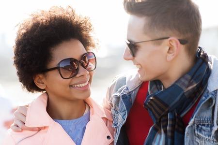 familia abrazo: amistad, las relaciones, el turismo, los viajes y el concepto de la gente - grupo de amigos adolescentes felices o pareja con gafas de sol hablando al aire libre