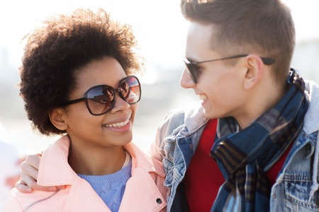 friendship, relations, tourism, travel and people concept - group of happy teenage friends or couple in sunglasses talking outdoors Stock Photo