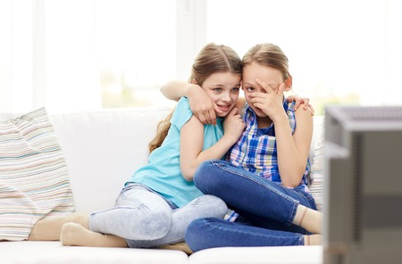 fear child: people, children, television, friends and friendship concept - two scared little girls watching horror on tv at home
