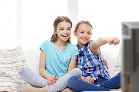 사람, 어린이, 텔레비전, 친구들과 우정 개념 - 두 행복 어린 소녀 TV를보고, 집에서 손가락을 가리키는
